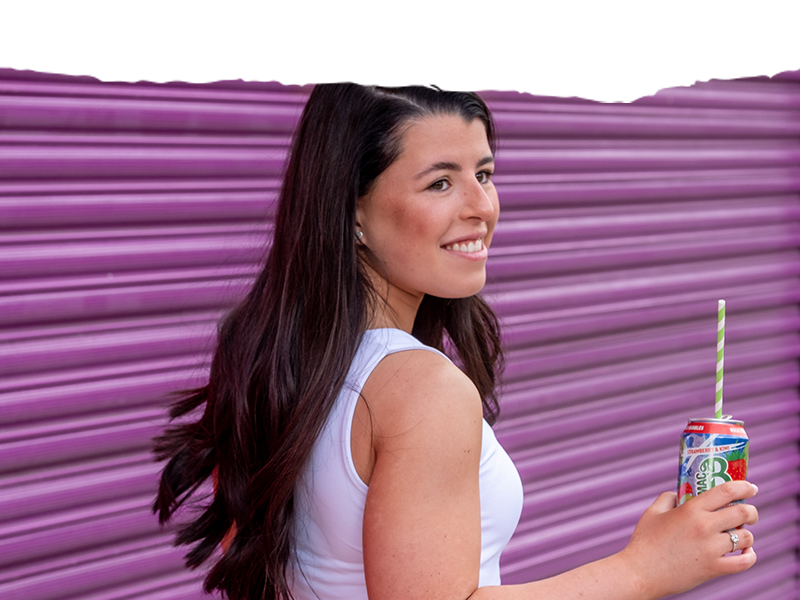 A young woman drinking from a can of sparkling Macb water with a straw
